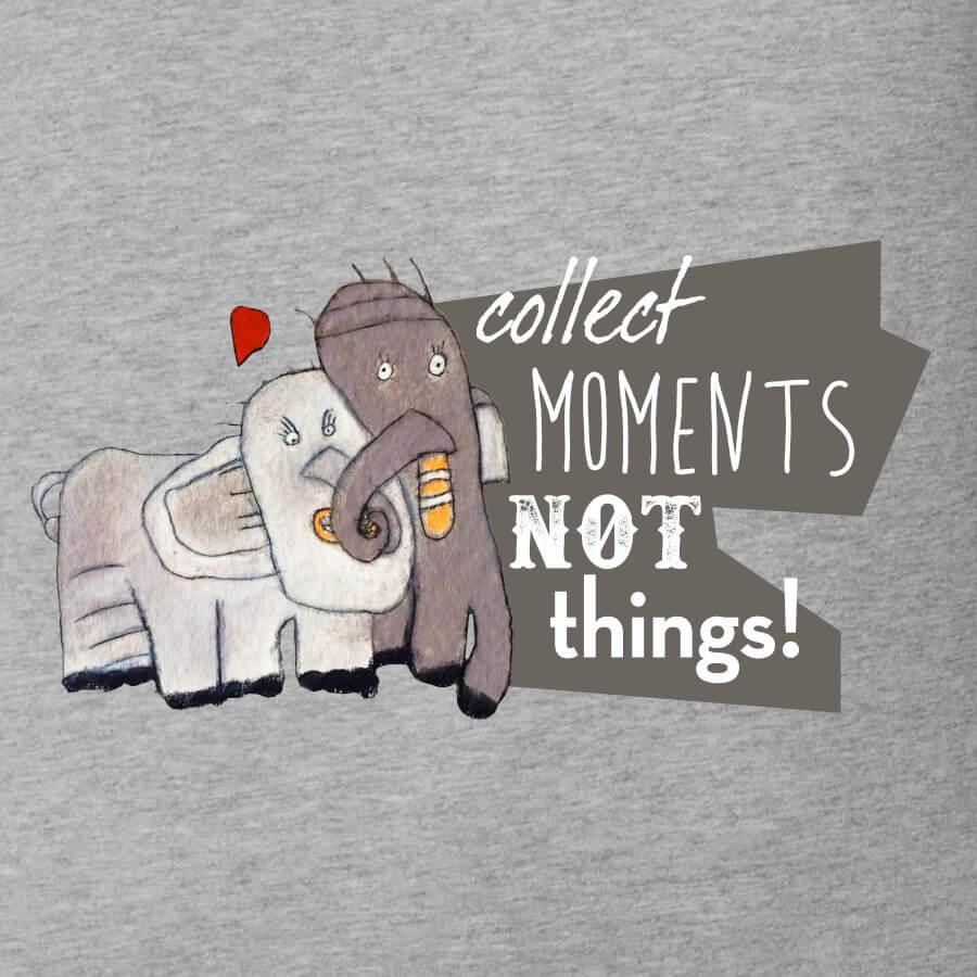 Zwei Elefanten in Weiß und Grau mit verschlungenen Rüsseln. Zwei rote Herzen schweben über ihnen. Das Motiv heißt Elefantenliebe und wurde für den Valentinstag kreiert. Der Spruch dazu heißt Collect Moments not Things.
