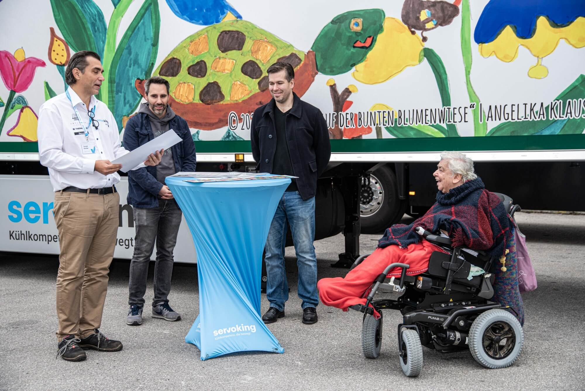 Gerakd Bucher von Servoking überreicht Künstlerin Lisi Hinterlechner die Urkunde für den 3. Platz beim VOI fesch Kunstpreis. Im Hintergrund stehen Christian Hammer von echtleinwand.at und Helmuth Stöber von VOI fesch.