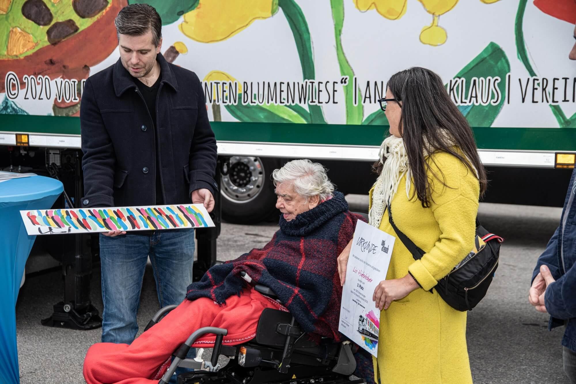 """Christian Hammer von echtleinwand.at überreicht Lisi Hinterlechner eine Reproduktion ihres Kunstwerkes """"Rot"""""""