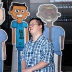 Künstler David Cheng steht vor den Pappaufstellern mit den Menschen, welche er gezeichnet hat.