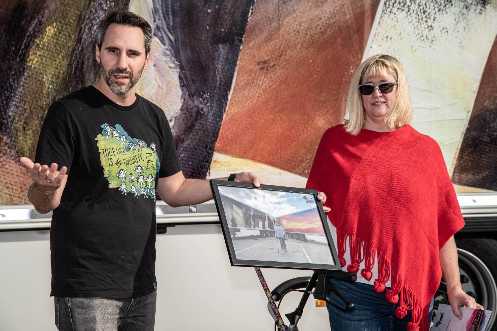 Helmuth Stöber und Künstlerin Brigitte Riedel halten gemeinsam ein Bild. Auf dem Bild sieht man Brigitte vor den 2 LKWs stehen, welche mit ihren Kunstwerken beklebt sind.