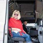 Künstlerin Brigitte Riedel sitzt im Beifahrersitz vom LKW bei offener Türe. Hinter Ihr sitzt der LKW-Fahrer.