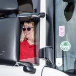 Brigitte Riedel sitzt mit einer Sonnenbrille im Sattelaufleger und lacht.