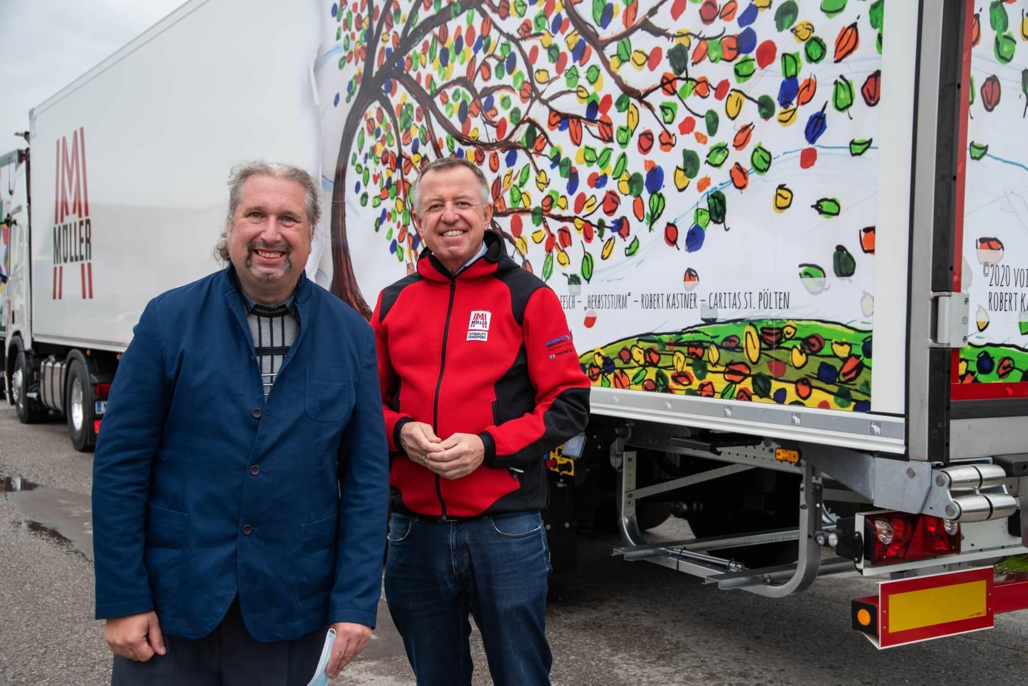 Künstler Robert Kastner mit Fritz Müller, dem Geschäftsführer von Müller Transporte. Das Unternehmen hat das Motiv Herbststurm für einen LKW ausgewählt, welcher im Hintergrund zu sehen ist.
