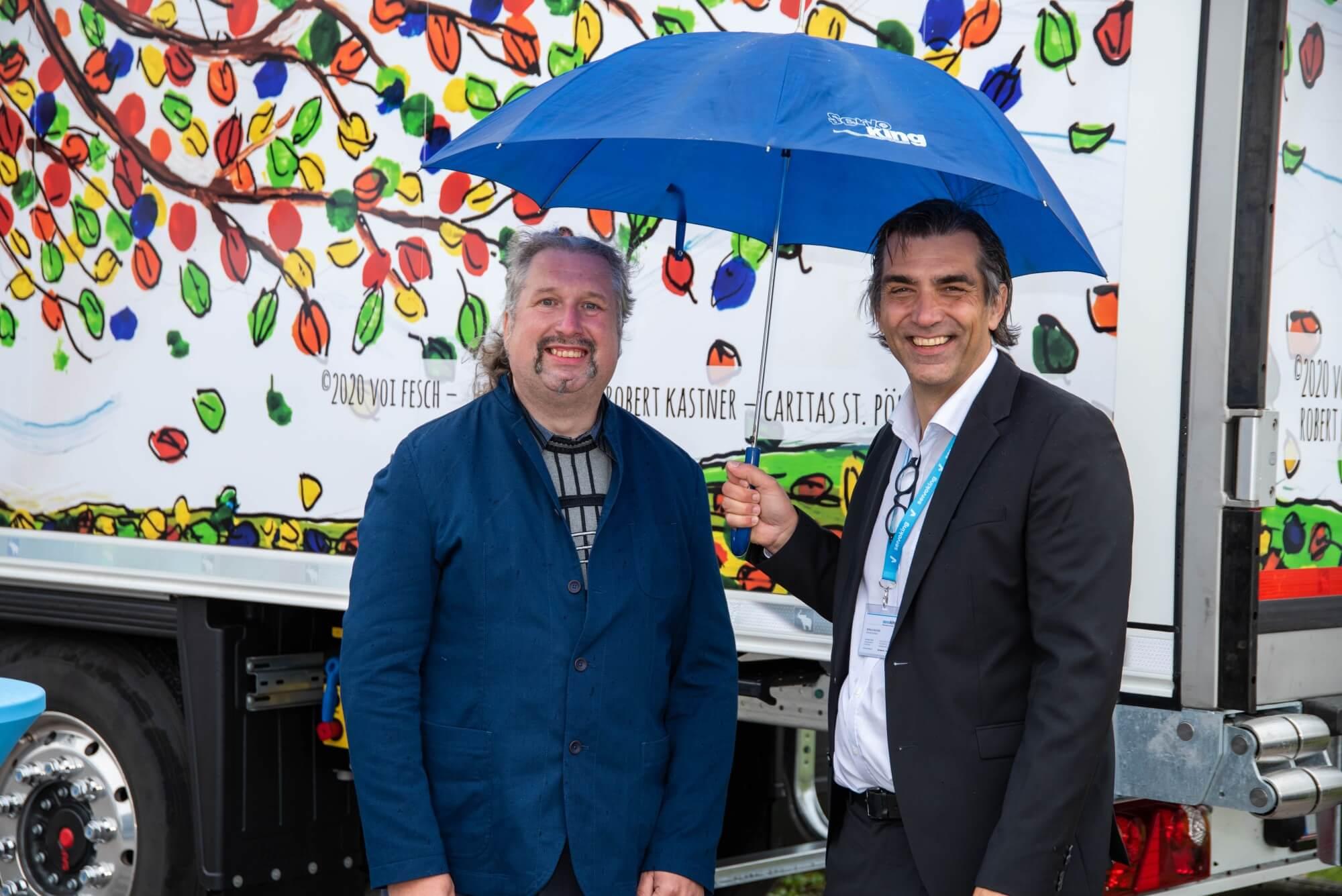 Künstler Robert Kastner mit Servoking Geschäftsführer Gerald Bucher, welcher einen blauen Regenschirm hält.