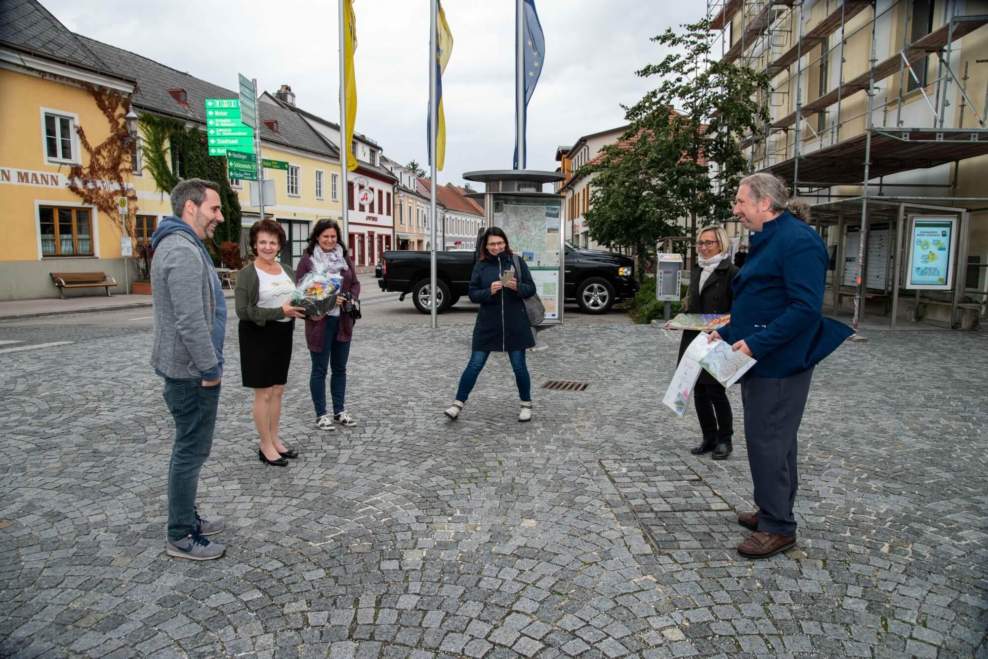 Teilnehmer der Preisverleihung stehen in einem Kreis auf dem Hauptplatz von Gföhl.