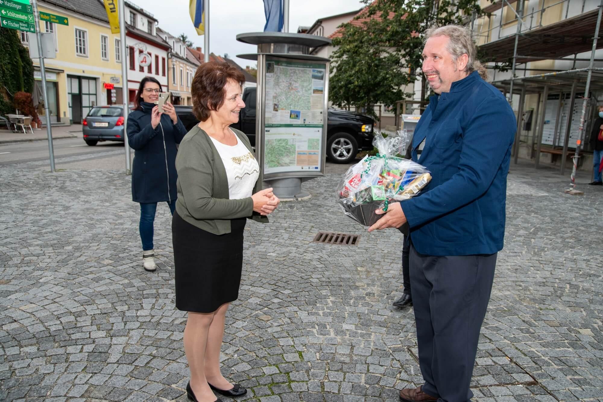 Die Bürgermeisterin von Gföhl, Ludmilla Etzenberger, überreicht Robert Kastner einen Geschenkekorb.