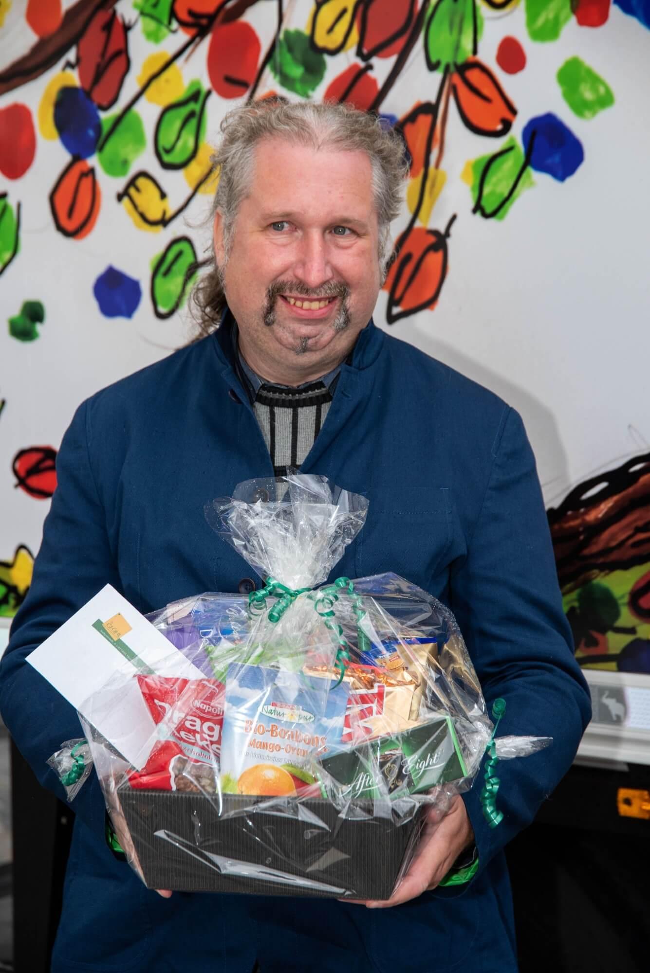Künstler Robert Kastner mit einem Geschenkekorb
