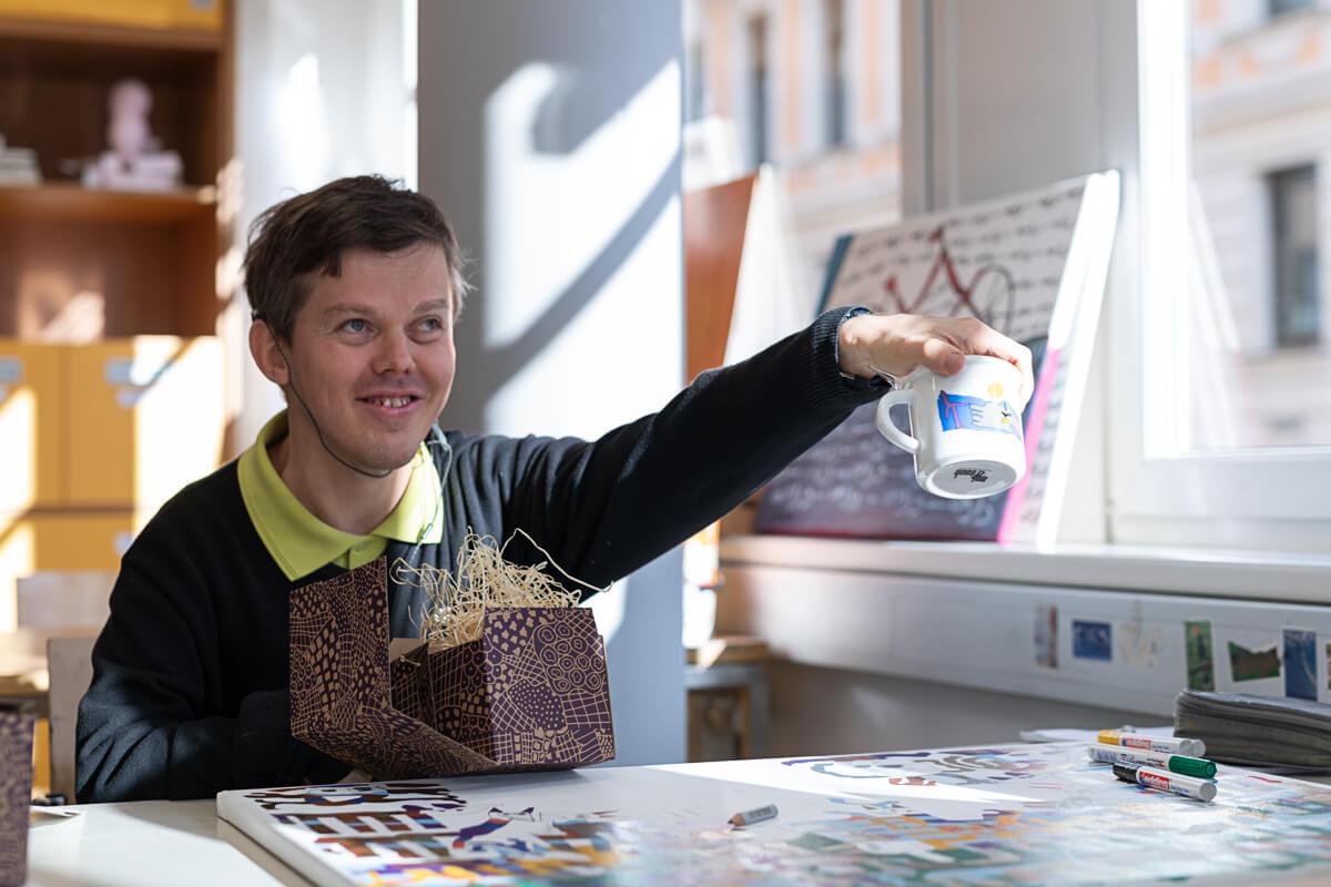 Künstler Max Nemeczek zeigt ein Häferl mit seinem Kunstwerk