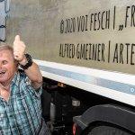 """Künstler Alfred Gmeiner zeigt einen Daumen hoch vor dem LKW mit seinem Kunstwerk """"Powerfrauen"""""""