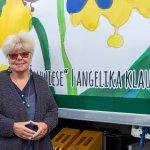 """Angelika Klaus vor dem LKW mit ihrem Motiv """"Blumenwiese"""""""