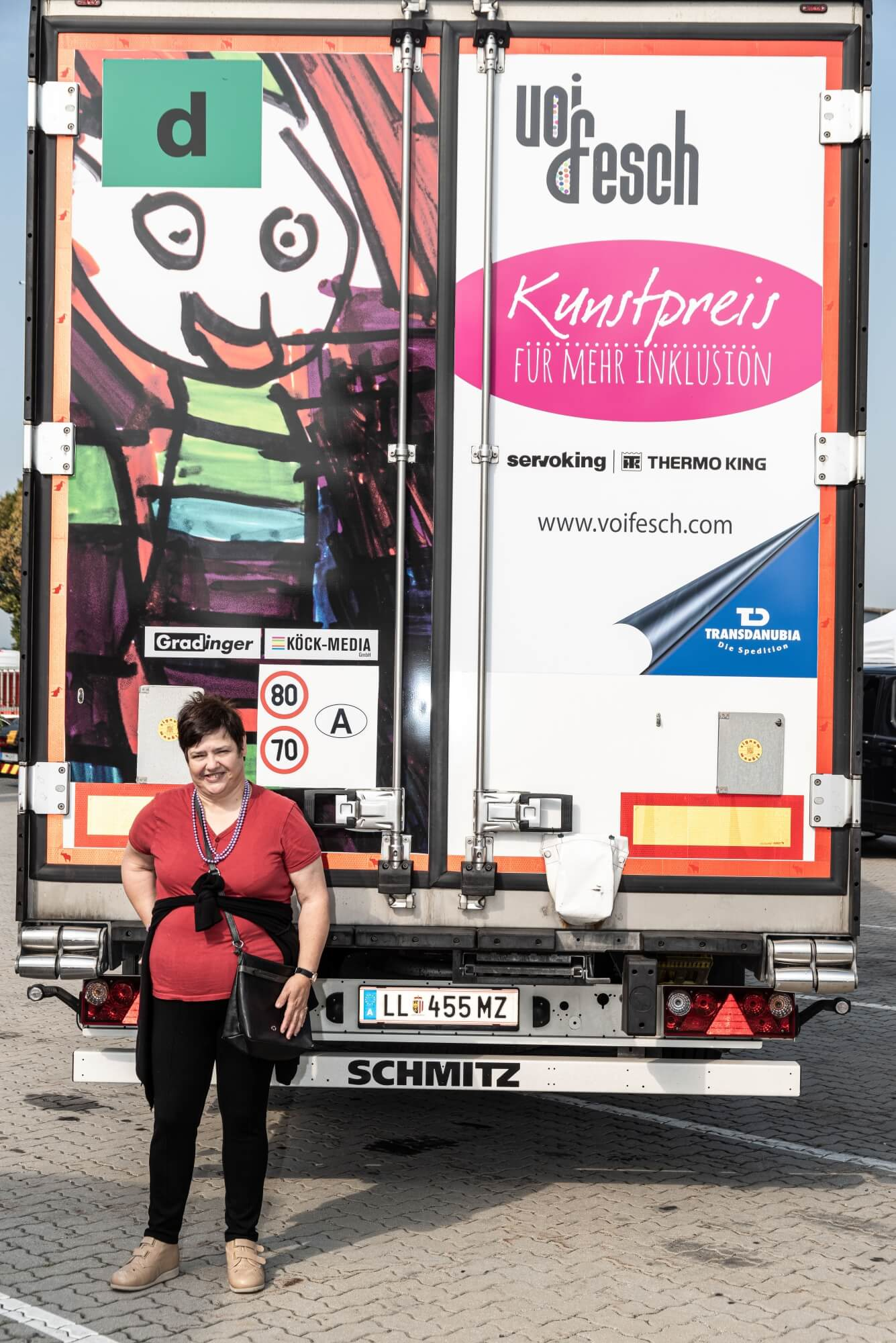 Künstlerin Monika Schmidhofer steht vor der Rückseite des LKWs, welcher mit ihrem Kunstwerk bedruckt ist. Zu sehen sind auch Logos von den Sponoren Servoking, Transdanubia und vom Kunstpreis Organisator VOI fesch.