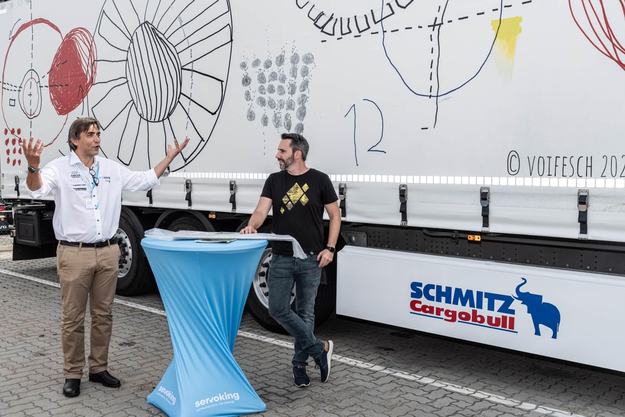 """Gerald Bucher, Geschäftsführer von Servoking hält eine Rede. Neben ihm steht Helmuth Stöber, Initiator von VOI fesch. Hinter ihnen ist der LKW mit dem Motiv """"Verbindungen"""" von Künstler Christoph Dietrich zu sehen."""
