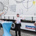 """VOI fesch Initiator Helmuth Stöber zeigt auf den LKW mit dem Motiv """"Verbindungen"""". Neben ihm steht der Künstler Christoph Dietrich, welcher das Motiv gemalt hat. Es zeigt kreise und verschiedene geometrische Formen."""