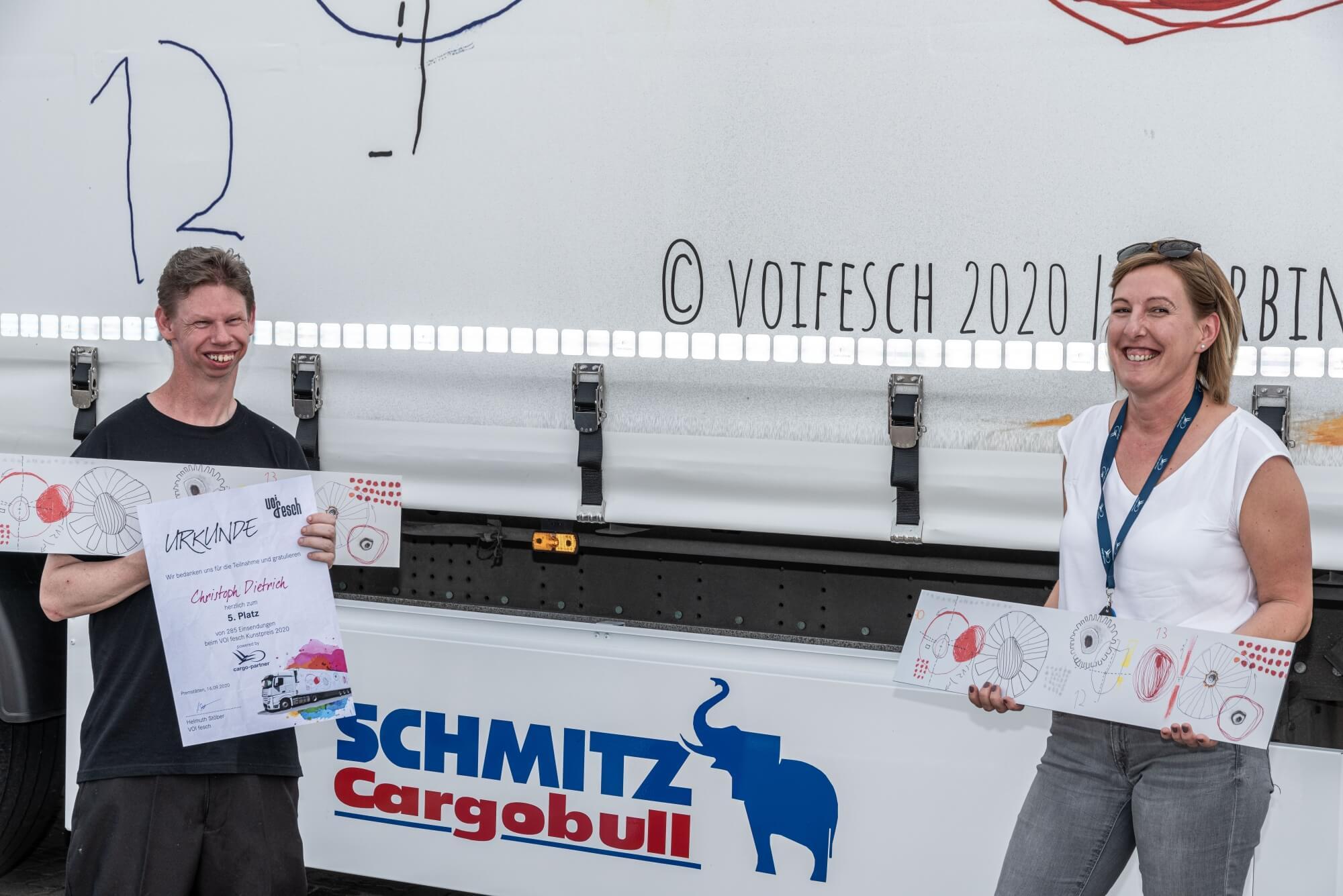 """Künstler Christoph Dietrich zeigt seine Urkunde vor dem LKW, welcher mit seinem Motiv """"Verbindungen"""" bedruckt ist. Er hält auch ein Bild von seinem Bild, welches von EchtLeinwand bedruckt wurde. Neben ihm steht Csilla Steuer von Cargopartner."""