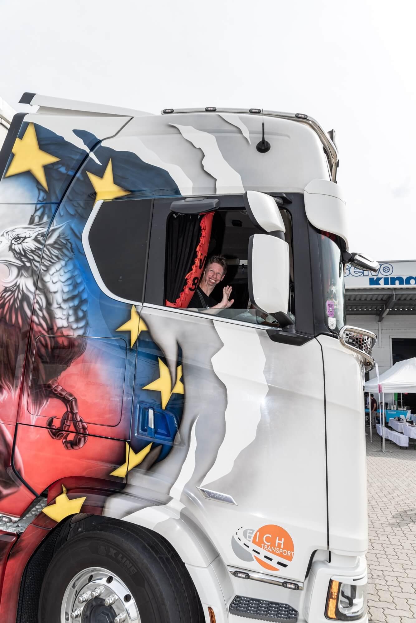 Christoph Dietrich sitzt lächelnd im LKW und winkt. Der LKW ist bunt bemalt.
