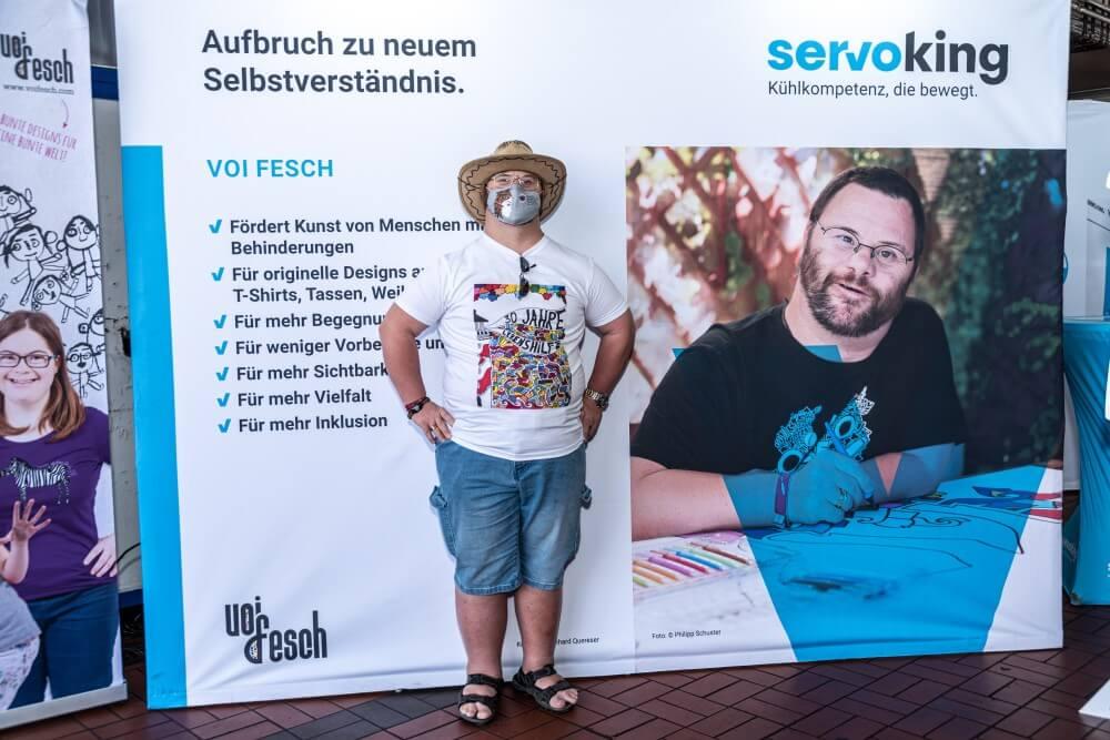 Künstler Berhard Quereser steht vor einem Plakat, auf welchem ein Bild von ihm beim Zeichnen abgebildet ist. Bernhard Quereser trägt eine Mund-Nasen-Schutz Maske, welche er für das Frauen Kompetenz Zentrum entworfen hat.