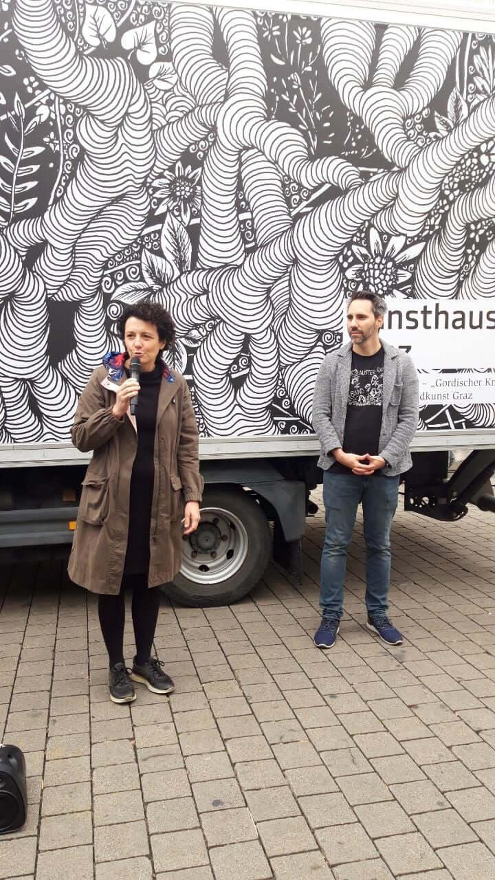 Susanne Maurer-Aldrian (Geschäftsführer*in der Lebenshilfen Soziale Dienste) gratuliert den beiden Randkunst-Künstler*innen. Neben ihr steht Helmuth Stöber, Gründer von VOI fesch.