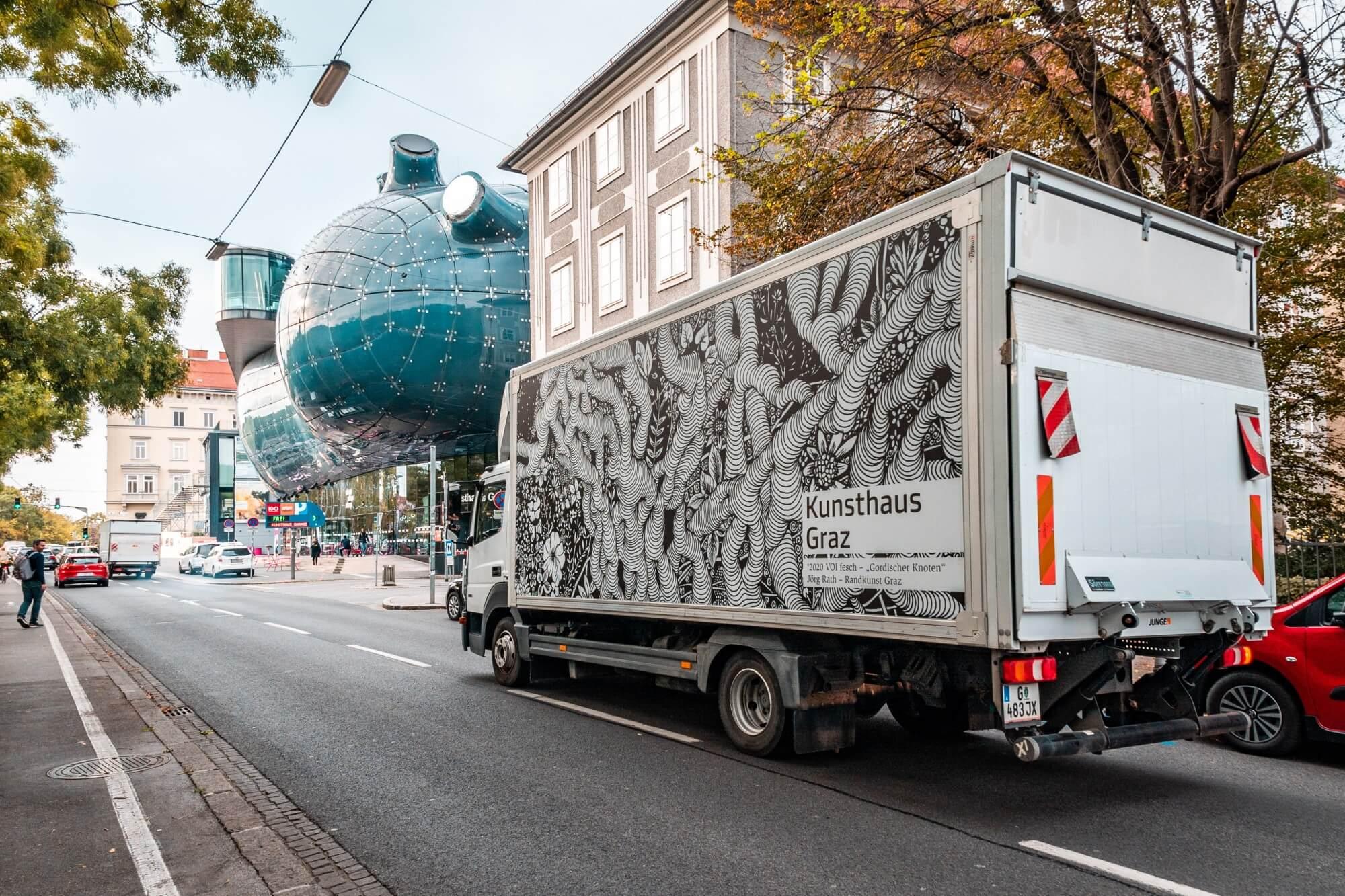 """Der LKW vom Kunsthaus Graz, welcher mit dem Motiv """"Gordischer Knoten"""" von Jörg Rath beklebt ist. Im Hintergrund ist das Gebäude vom Kunsthaus Graz zu sehen."""