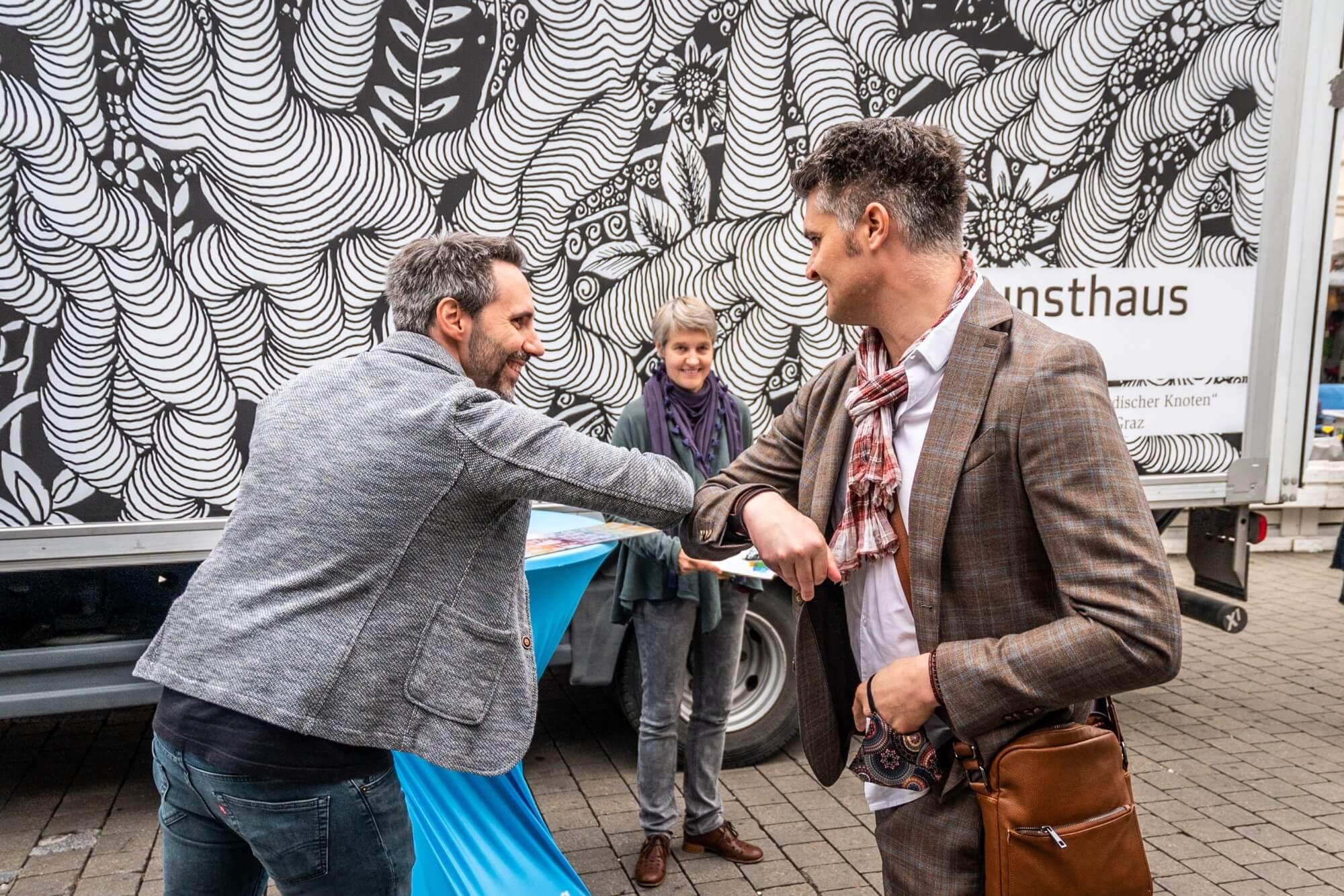 Helmuth Stöber von VOI fesch grüßt Künstler Jörg Rath mit einem Ellbogengruß