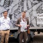 """Gerald Bucher mit Jörg Rath. Der Künstler hät seine Urkunde. Im Hintergrund steht der LKW, welcher mit Jörg Rath's Motiv """"Gordischer Knoten"""" beklebt ist."""