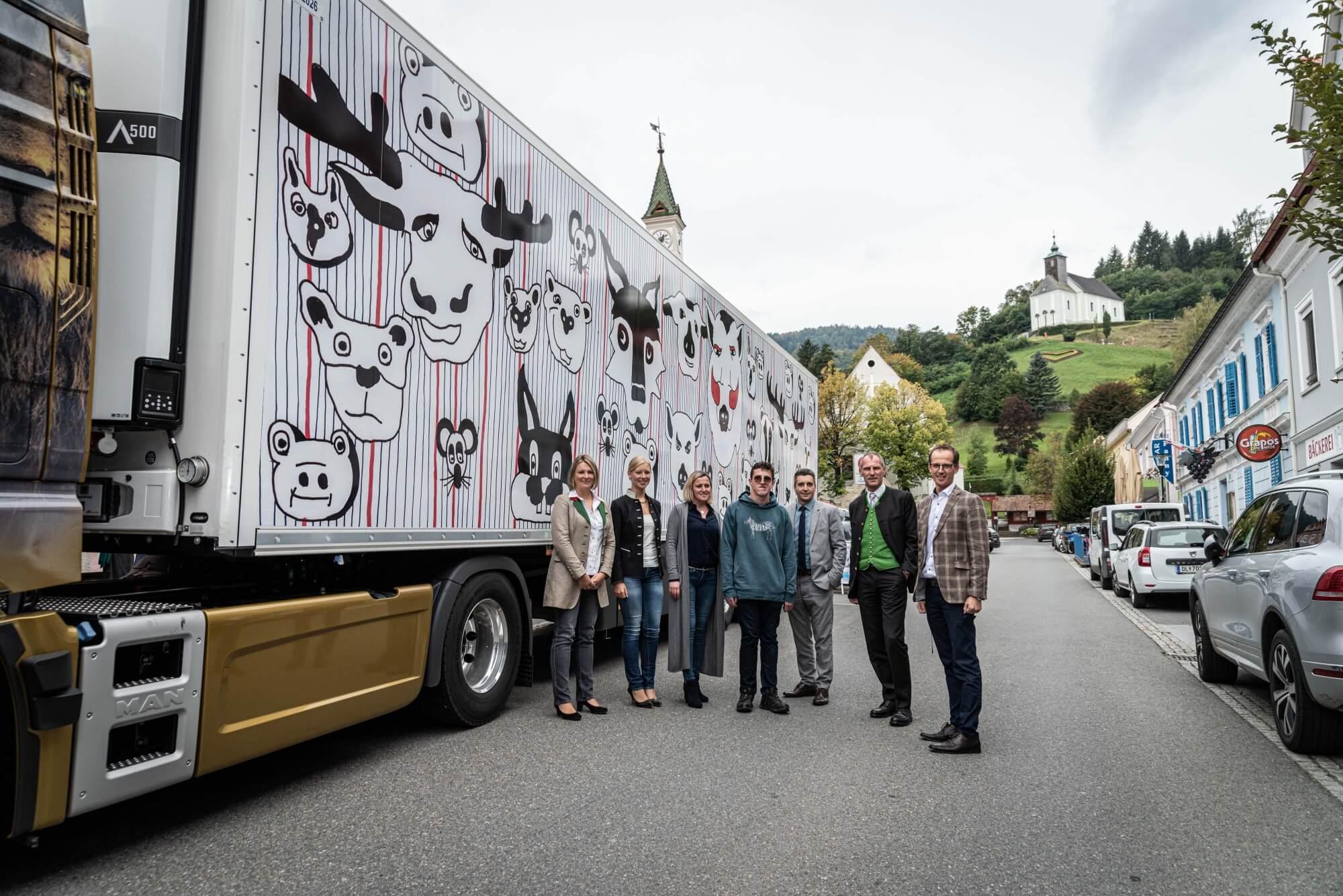 Ein Gruppenfoto mit dem Bürgermeister von Bad Schwanberg, Karlheinz Schuster. Im Hintergrund ist der bunt beklebten LKW am Hauptplatz von Bad Schwanberg zu sehen.