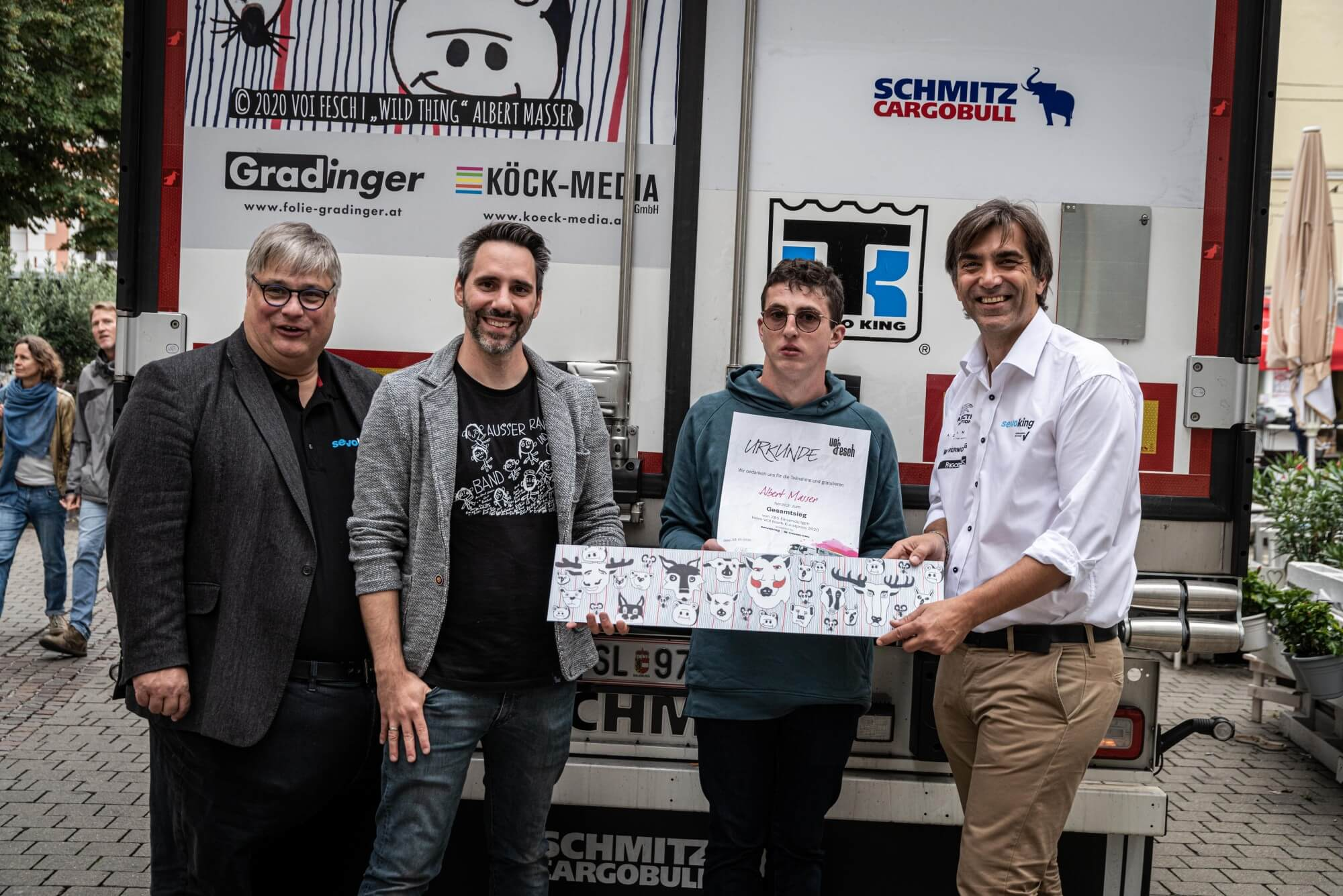 Ein Gruppenfoto vor der Rückseite des bedruckten LKW. Zu sehen sind Christian Mahr von Servoking, Helmuth Stöber von VOI fesch, Künstler Albert Masser und Servoking Geschäftsführer Gerald Bucher.