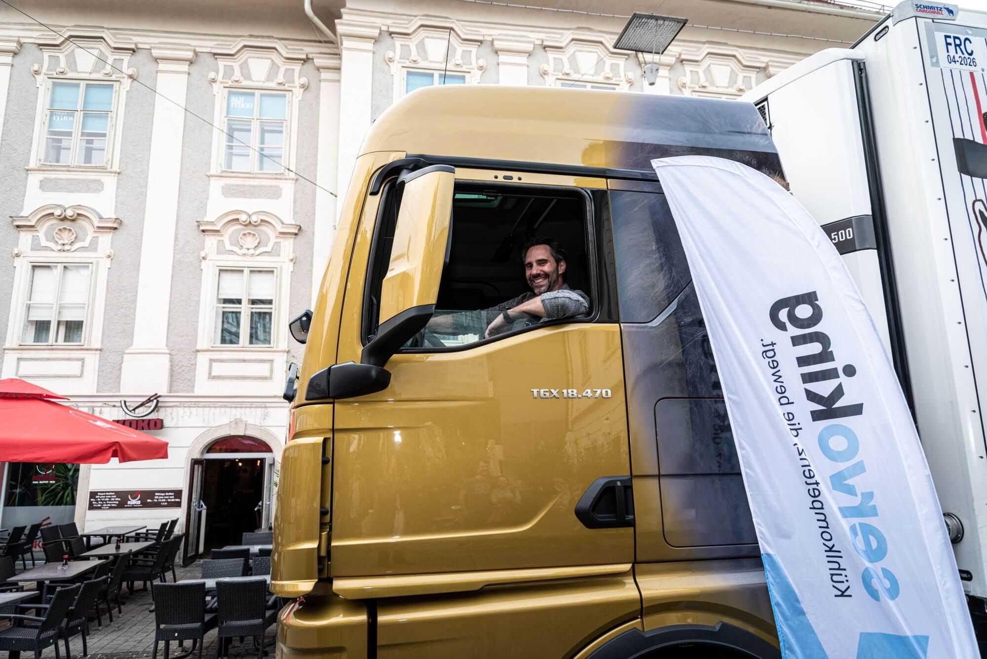 Kunstpreis Mit-Initiator Helmuth Stöber macht eine Sitzprobe im LKW. Im Hintergrund ist ein Gebäude der Grazer Innenstadt.